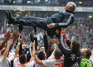 Bayern Munich's players throw coach Jupp Heynckes in the air after winning their German Bundesliga match against Eintracht Frankfurt and the league in Frankfurt on Saturday