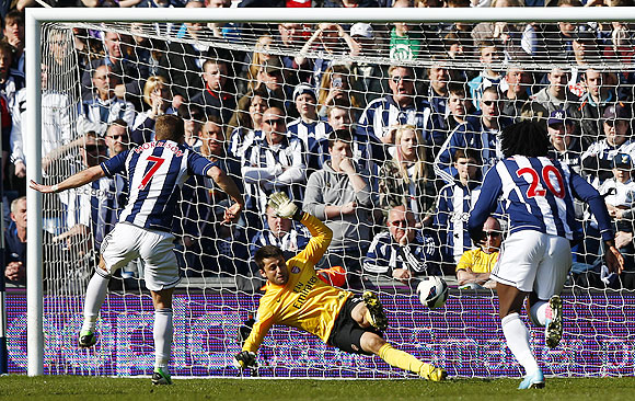 West Bromwich Albion's James Morrison (left) scores a penalty past Arsenal's Lukasz Fabianski during their English Premier League match at the Hawthorns in West Bromwich, on Saturday