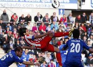 Atletico Madrid's Radamel Falcao (centre) tries to kick the ball between Getafe's Albert Lopo (left) and Juan Valera