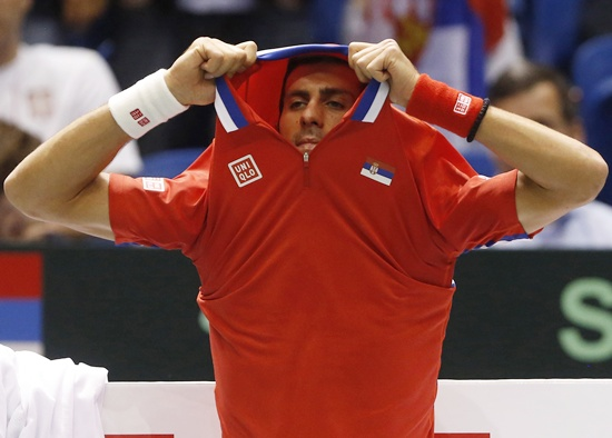 Serbia's Novak Djokovic takes off his shirt