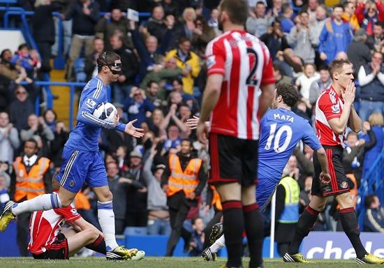 Fernando Torres of Chelsea runs the ball back to the centre spot after   Matt Kilgallon (right) of Sunderland scored an own goal
