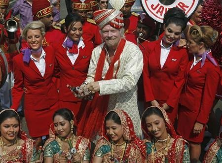 Virgin Group founder Richard Branson poses with his crew members and a group of Indian folk artists (bottom) during a promotional event in Mumbai October 26, 2012