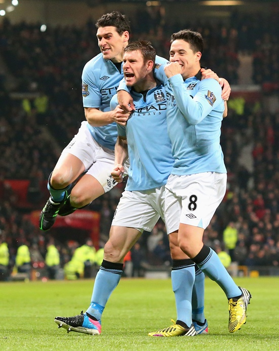 James Milner of Manchester City celebrates with his team-mates Gareth Barry (left) and Samir Nasri