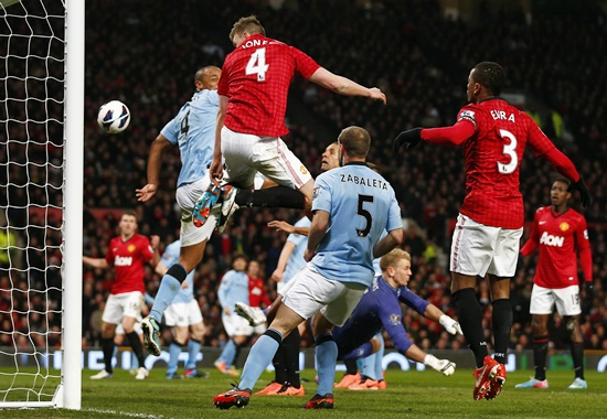 Manchester United's Phil Jones (centre) heads onto the back of Manchester City's Vincent Kompany to score