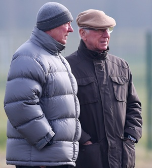 Sir Alex Ferguson the manager of Manchester United talks with Sir Bobby Charlton