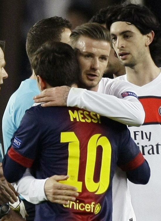 Paris St Germain's David Beckham embraces Barcelona's Lionel Messi