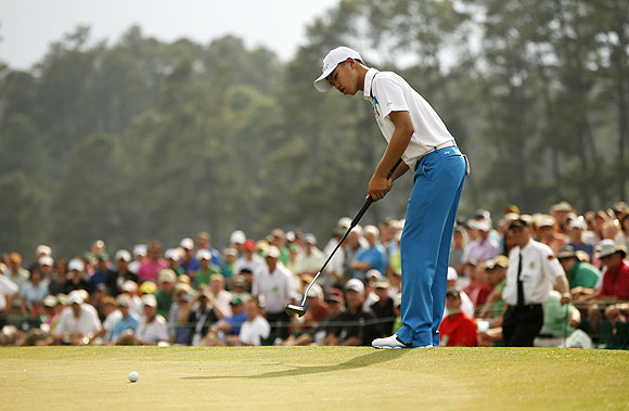 Fourteen-year-old amateur Guan Tianlang of China sinks a birdie putt on the 18th green during first round play in the 2013 Masters golf tournament at the Augusta National Golf Club in Augusta, Georgia, on Thursday