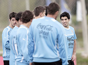 Luis Suarez (right) of Uruguay's chats with teammates during a training session