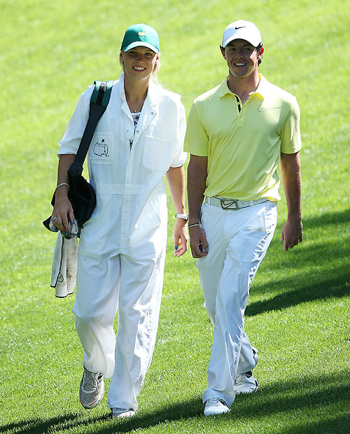 Rory McIlroy walks with his caddie and girlfriend Caroline Wozniacki during the Par 3 Contest prior to the start of the 2013 Masters Tournament at Augusta National Golf Club