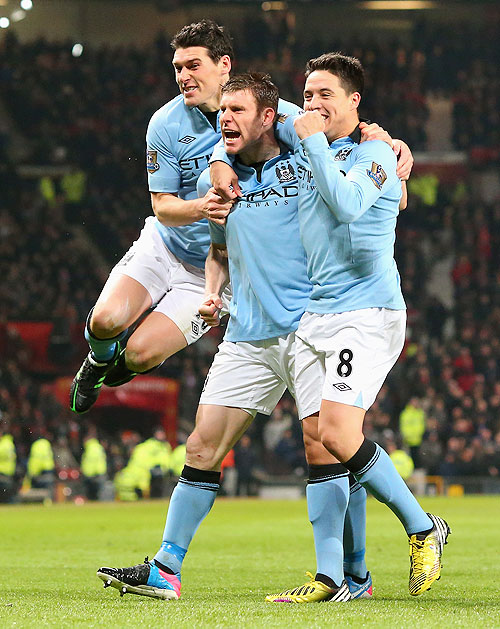 James Milner of Manchester City celebrates with teammates Gareth Barry (left) and Samir Nasri (right)