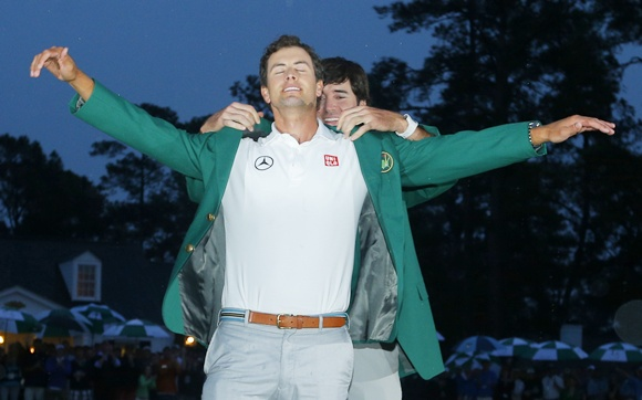 Adam Scott of Australia (left) receives his green jacket from 2012 champion Bubba Watson