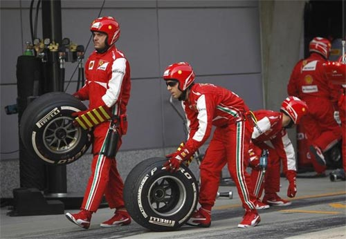 Team members of Ferrari Formula One driver Fernando Alonso of Spain roll tyres in the pit lane