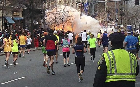 Runners continue to run towards the finish line of the   Boston Marathon as an explosion erupts near the finish line