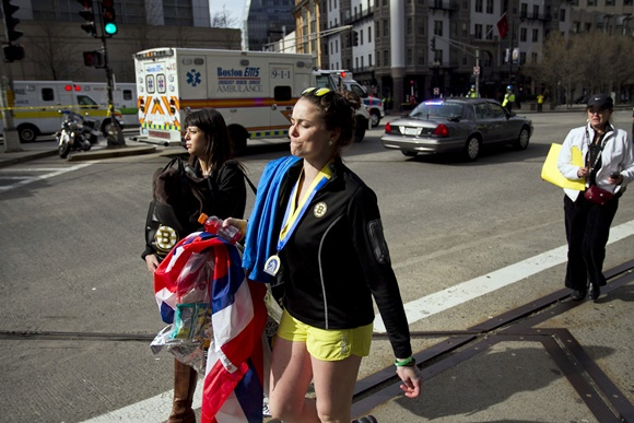 A woman walks past an ambulance at the scene after explosions   reportedly interrupted the running of the 117th Boston Marathon