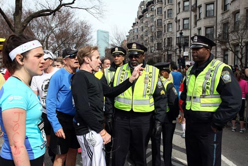 Runners talk to Boston Police near Kenmore Square after two bombs exploded during the 117th Boston Marathon