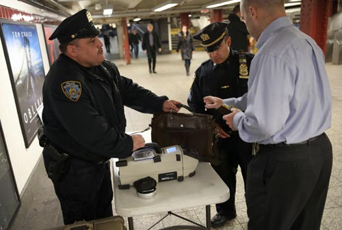 Police check a subway passenger's bag at Penn Station