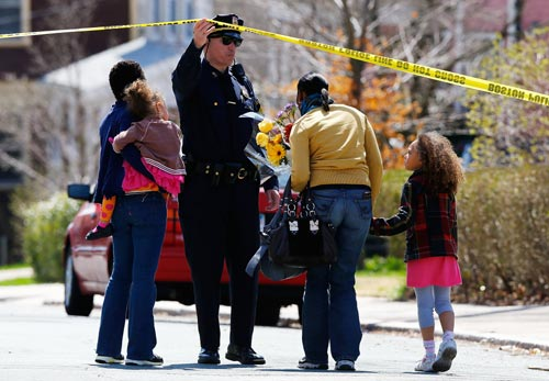 A Boston Police officer lifts the tape for a family to leave flowers in front of the home of the Richard family whose eight-year-old son, Martin, was killed by an explosion