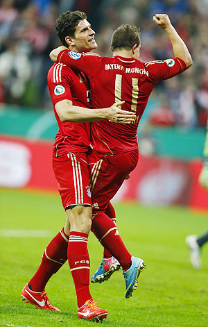 Bayern Munich's Xherdan Shaqiri (right) celebrates with Mario Gomez after a goal against Wolfsburg during their German soccer cup (DFB Pokal) semi-final match in Munich on Tuesday
