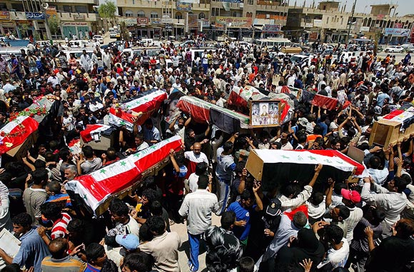 Iraqis carry coffins containing the remains of members of the Iraqi taekwondo national team in Baghdad, on June 16, 2007.