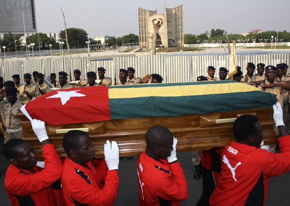 Pallbearers carry the coffin of Togo soccer team's assistant coach Amalete Abalo during the funeral service in front of Congress Palace in Lome, on January 15, 2010.