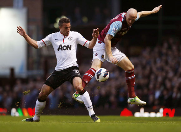 West Ham United's James Collins (right) challenges Manchester United's Robin van Persie during their English Premier League match at The Boleyn Ground on Wednesday