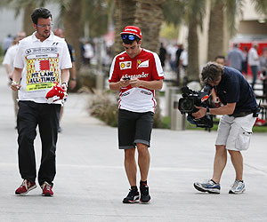 Ferrari'S Fernando Alonso (centre) checks his mobile phone in the paddock at the Bahrain International Circuit on Thursday