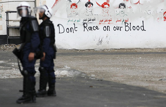 Riot police officers stand near an anti-Formula One graffiti during an anti-government protest in the village of Diraz west of Manama on Friday