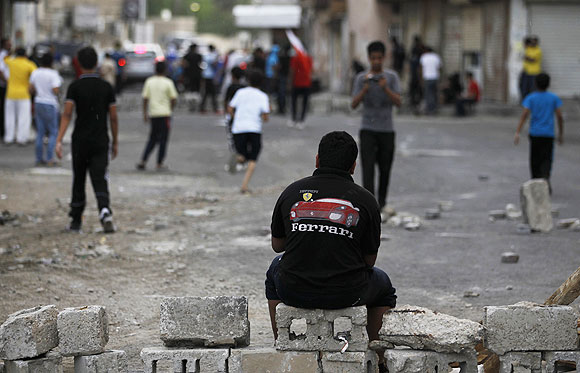 A protester wearing a Ferrari t-shirt sits on a block during an anti-government demonstration in the village of Diraz west of Manama on Thursday