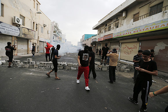 Anti-government protesters stand in front of a teargas cloud fired by riot police during a demonstration in the village of Diraz west of Manama on Thursday