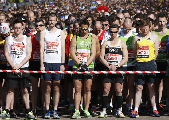 Runners observe a moment of silence before the start of the London Marathon