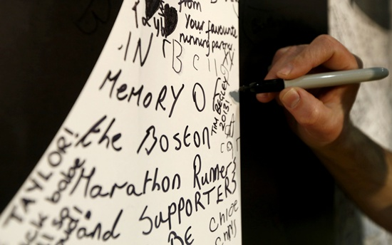 People write on a wall of encouragement, including messages to victims of the Boston bombing