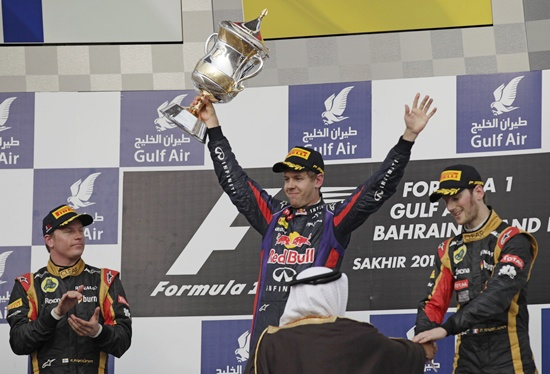 Winner Red Bull Formula One driver Sebastian Vettel (centre) celebrates with the winner's trophy beside second placed Lotus driver Kimi Raikkonen of Finland (left) and third placed Lotus driver Romain Grosjean