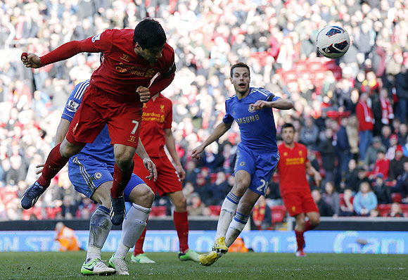 Liverpool's Luis Suarez (left) scores against Chelsea during their English Premier League match at Anfield on Sunday