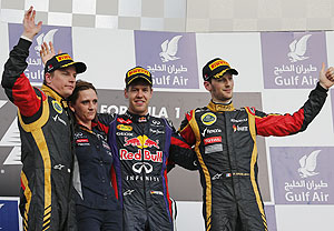 Red Bull's Sebastian Vettel (2nd from right), Lotus' Kimi Raikkonen (left) and Romain Grosjean (right) celebrate with Red Bull Formula One's Head of Trackside Electronics Gill Jones during the victory ceremony at the Sakhir circuit during the Bahrain GP on Sunday