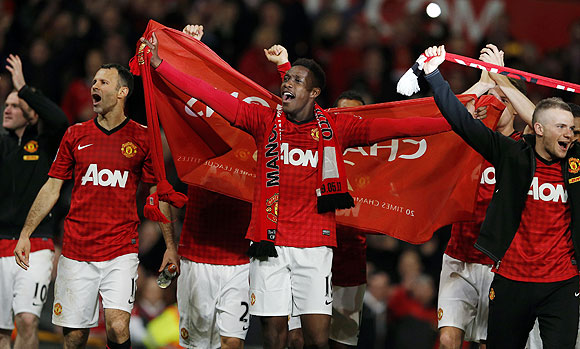 Manchester United's Ryan Giggs (left), Danny Welbeck (centre) and Tom Cleverley celebrate after clinching the English Premier League title Old Trafford on Monday