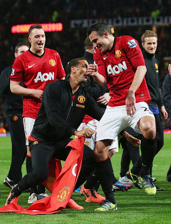 Manchester United's Rio Ferdinand jokes with teammate Robin van Persie on Monday