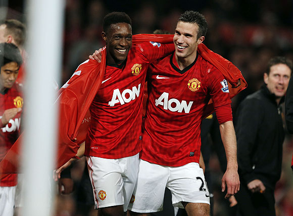 Manchester United's Robin Van Persie (right) celebrates with teammate Danny Welbeck after clinching the English Premier League title on Monday
