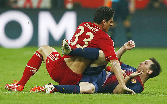 Bayern Munich's Mario Gomez (left) falls on top of Barcelona's Lionel Messi during their Champions League semi-final first leg match in Munich, on Tuesday
