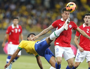 Brazil's Paulinho (left) tries to clear the ball away from by Chile's Eduardo Vargas (centre) and Eugenio Mena