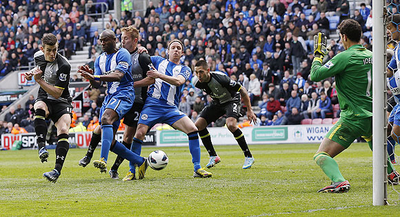 Wigan Athletic's Emmerson Boyce (2nd from left) deflects the ball past his goalkeeper Joel Robles (right) to concede an own goal during their English Premier League match against Tottenham Hotspur on Saturday