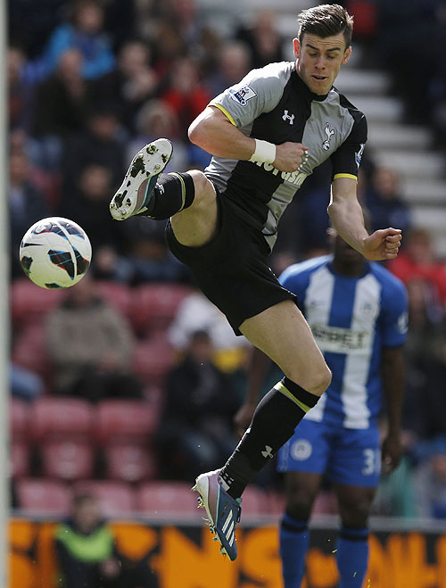 Tottenham Hotspur's Gareth Bale charges down a clearance from Wigan Athletic's goalkeeper Joel Robles to score during their English Premier League match on Saturday