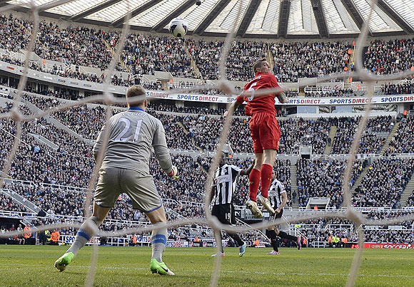 Liverpool's Daniel Agger (right) heads to score against Newcastle United during their English Premier League match on Saturday