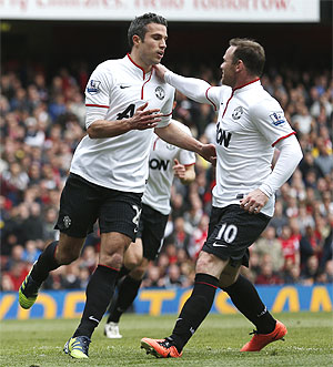 Manchester United's Robin van Persie (left) is congratulated by teammate Wayne Rooney after scoring against Arsenal during their English Premier League match at Emirates Stadium on Sunday
