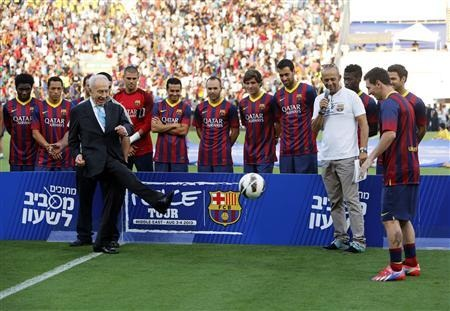 Israel President Shimon Peres (L) kicks the ball to Barcelona's Lionel Messi (R) at the opening of a soccer clinic with Arab and Jewish children at Bloomfield stadium in Tel Aviv August 4, 2013.