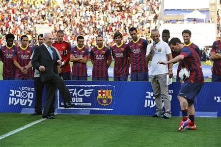 President Shimon Peres (L) kicks the ball directly into Messi's midriff