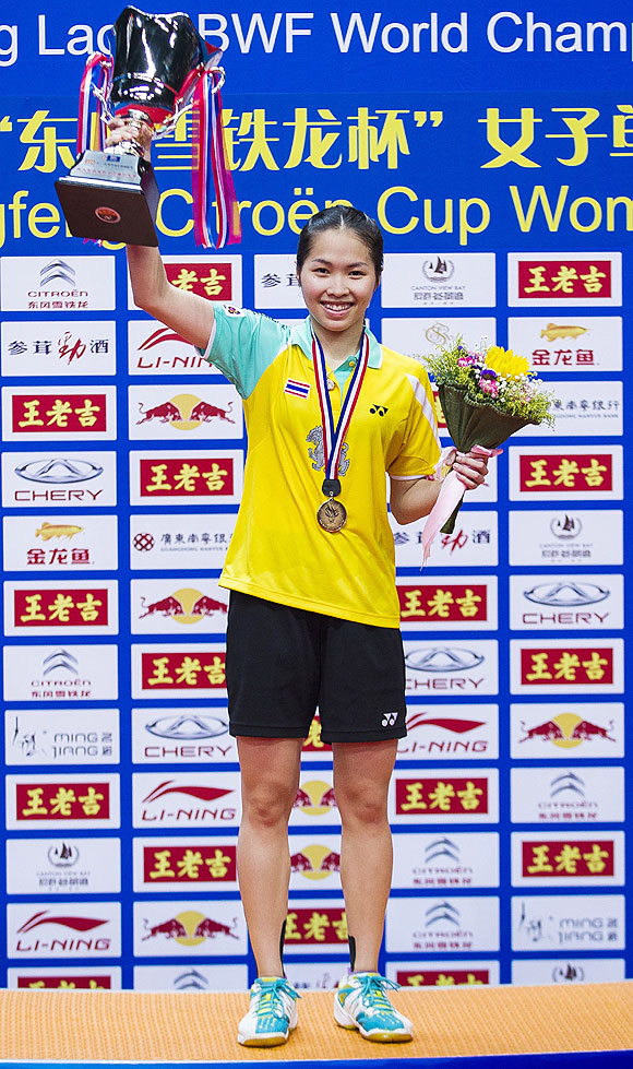 Ratchanok Intanon of Thailand poses on the podium with the trophy after winning her women's singles final match against Li Xuerui of China during the Badminton World Championships at the Tianhe Gymnasium in Guangzhou, on Sunday
