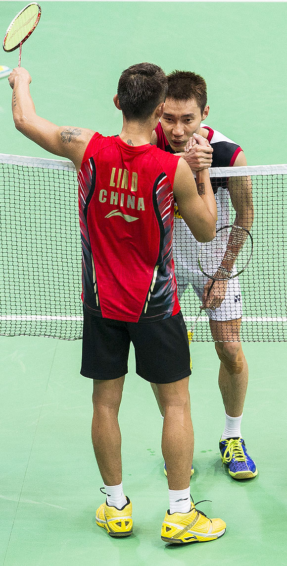 Lee Chong Wei of Malaysia (right) congratulates Lin Dan of China before retiring injured during the men's singles final at the Tianhe Gymnasium in Guangzhou, on Sunday