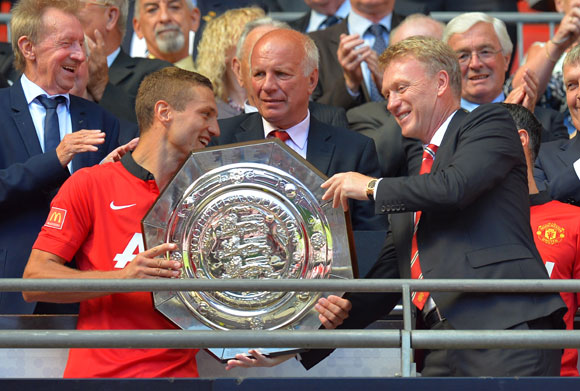 Nemanja Vidic of Manchester United and manager David Moyes with the trophy after victory