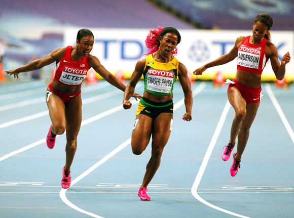 Shelly-Ann Fraser-Pryce of Jamaica (centre) crosses the line to win gold in the women's 100 metres