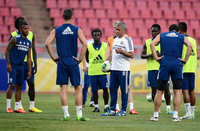 Jose Mourinho speaks to Chelsea's players during a training season